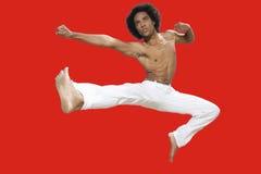Kickboxer, das über roten Hintergrund springt Lizenzfreie Stockbilder