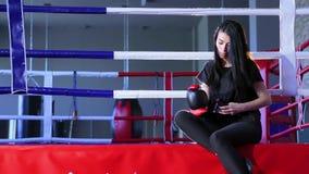 Kickboxer de la muchacha que se sienta en el anillo antes de entrenar