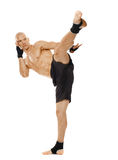 Kickboxer executing a powerful kick Royalty Free Stock Image