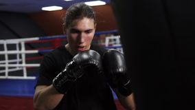 Kickboxer hits boxing pear. An angry boxer puts a punch in a boxing bag in black gloves. Workout in the gym.  stock video footage