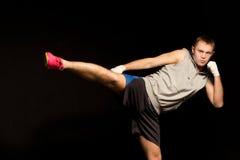 Kickboxer joven ágil que azota hacia fuera con su pie Fotos de archivo