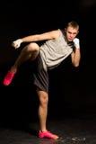 Kickboxer joven atlético que golpea con el pie durante una lucha Imágenes de archivo libres de regalías