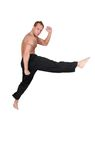 Kickboxer man. One adult topless kickboxing man jump kick over white Stock Photography