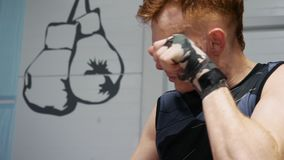 Kickboxer man massaging face before fight training in gym. Boxer man doing warm up exercise at boxing rig in fight club. Sport lifestyle stock footage