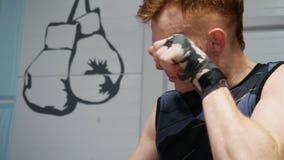 Kickboxer-Mann, der Gesicht vor Kampftraining in der Turnhalle massiert Boxermann, der Aufwärmenübung an der Verpackenanlage im K stock footage