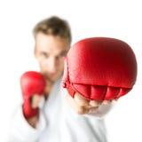 Kickboxer mit den roten Boxhandschuhen, die einen Kampfkunstdurchschlag durchführen Lizenzfreie Stockfotografie