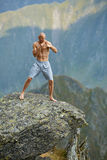 Kickboxer or muay thai fighter training on a mountain cliff Stock Image