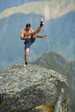 Kickboxer or muay thai fighter training on a mountain cliff Stock Photos