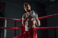 Kickboxer se tient dans le coin de l'anneau dans un support de attaque Image libre de droits