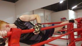 Kickboxer som sträcker benet för konkurrens i kampklubba Manboxareutbildning som sträcker övningen för ben medan boxning stock video