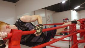 Kickboxer stretching leg before competition in fight club. Man boxer training stretching exercise for legs while boxing. Kickboxer fighter stretching leg before stock video