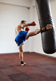 Kickboxer training with punchbag Royalty Free Stock Photography