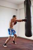 Kickboxer training with punchbag Stock Image