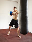 Kickboxer training with punchbag Stock Images