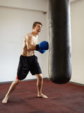 Kickboxer training with punchbag Royalty Free Stock Images