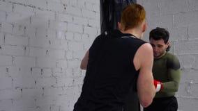 Kickboxer-Trainingstritt durch Verpackentasche auf kickboxing Training Boxerman in den Handschuhen, die Durchschläge tun, um Tasc