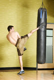 Kickboxer working out on punching bag Stock Photos