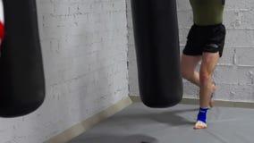 Kickboxermens opleidingsstempels door gevechtszak in gymnastiek Boksermens in handschoenen die aan ponsenzak in dozen doen in str stock videobeelden