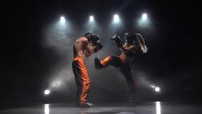 Kickboxing from the blow he falls to the floor. Smoke background. Slow motion. Light from behind. Girl is kicking the guy they are sparring for kickboxing from stock video