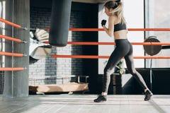Kickboxing-Frau in den airpods Sandsack Stärke-Sitzkörper des Eignungsstudios ausbildend im heftigen stockbilder