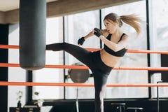 Kickboxing-Frauen-Trainingssandsack Stärke-Sitzkörper des Eignungsstudios im heftigen lizenzfreie stockfotos