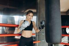 Kickboxing-Frauen-Trainingssandsack in Stärkesitzkörper kickboxer Reihe des Eignungsstudios heftiger lizenzfreie stockfotografie