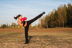 Kickboxing girl exercising high kick in summer nature. Beautiful kick boxing girl exercising high kick in the nature on sunny summer day Royalty Free Stock Photos