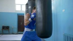 Kickboxing, individuo del combatiente resuelve golpes del boxeo en el saco de arena y entrena a los músculos del brazo antes de p metrajes