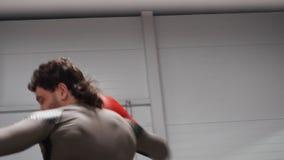 Kickboxing som munhuggas på cirkeln i kampklubban av sikten för två kämpar till och med rep stock video