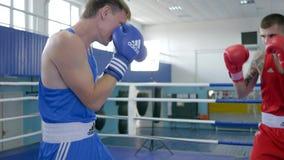 Kickboxing, técnica de la práctica de los atletas de los hombres del boxeador pega en el entrenamiento antes de partido en anillo metrajes