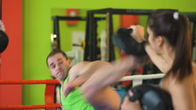 Kickboxing trainer man train with young woman in boxing ring stock video