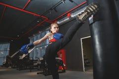 Kickboxing woman punching kicking bag at the gym stock photography