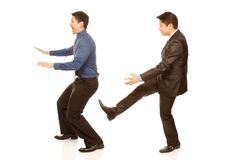 Kicked Out. A boss kicking out an employee (isolated on white Royalty Free Stock Photos