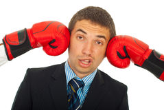 Kicked by two boxing gloves. Business man being kicked by two boxing gloves and making a face isolated on white background Stock Photography