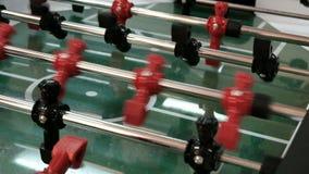 Kicker παιχνιδιών ποδοσφαίρου επιτραπέζιου ποδοσφαίρου με τους κόκκινους και μπλε παίκτες E Νέοι φίλοι που παίζουν το επιτραπέζιο φιλμ μικρού μήκους
