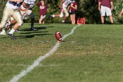 Kicker approaching football on a tee for kickoff. On the 40 yard line Stock Photography