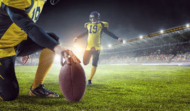 Kicker on his position. Mixed media. Two american football players starting game. Mixed media Royalty Free Stock Photos