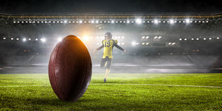 Kicker player on position. Mixed media. American football player in yellow sport wear. Mixed media Royalty Free Stock Photo