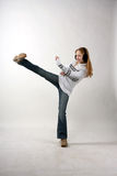 Kicking. A young woman in jeans and a sweater kick royalty free stock photography