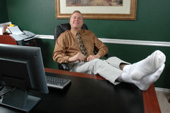 Kicking Back. Business man kicks off his shoes and leans back to relax at his desk royalty free stock photo