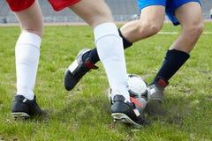 Kicking ball. Image of footballers legs kicking soccer ball on stadium Royalty Free Stock Photography