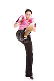 Kicking businesswoman with boxing gloves Stock Photos