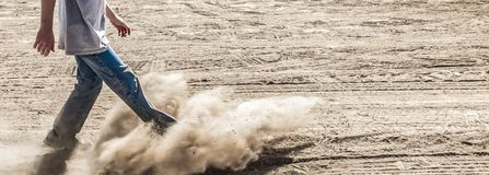 Kicking dirt. Young man (lower body only) in  blue jeans and trainers kicking up dust on a desert (sandy) road or track Stock Photography