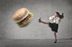 Kicking the hamburger. A girl is kicking a hamburger royalty free stock photography