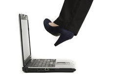 Kicking the laptop. Young business woman kicking her laptop Stock Image