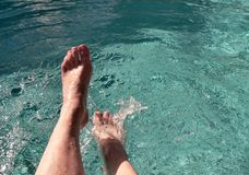 Kicking by the Pool. Fairskinned and freckled woman's feet splashing cool blue pool water in the sun stock image