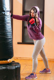 Kicking punching bag kickboxing female athlete Stock Photos