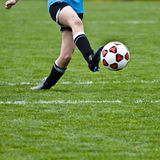 Kicking Soccer Ball. Female soccer player kicking the ball royalty free stock photography
