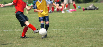 Kicking Soccer Ball on Field 2. Girl soccer player kicking ball during game play Royalty Free Stock Photography
