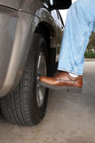 Kicking the tire. A man kicks his car tire to make sure it's inflated and and secured properly Royalty Free Stock Image
